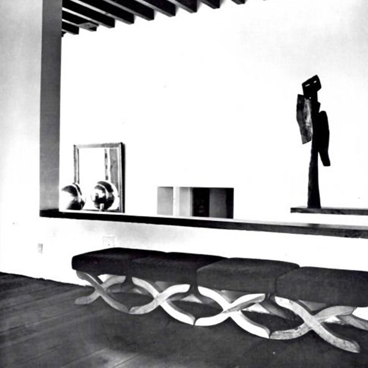 Casa Pedregal. An interior space. A black and white image. An upholstered, backless bench against a wall. An interior window-cill which holds two sculptures. The perspective of the photo allows for a suggestion of the interior rafters of the building.