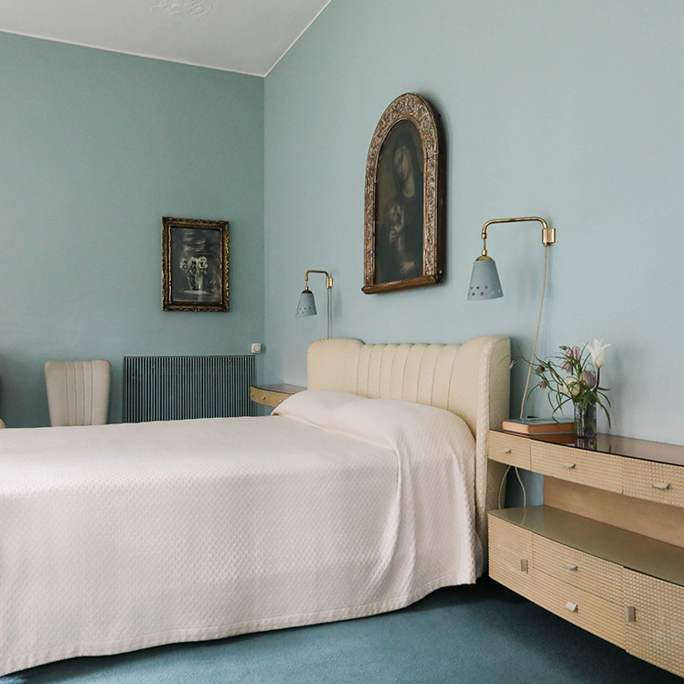 Interior scene of a bedroom in Villa Borsani. Double bed, with a leather bed frame. Two blue lights hang from the wall on either side of the bed. An ornamentally framed painting of The Virgin Mary holding Jesus Christ hangs above the bed. Pale blue wall. Dark blue carpets. Two modern wooden side cabinets are at either side of the bed. A vase of flowers on the cabinet in the foreground.