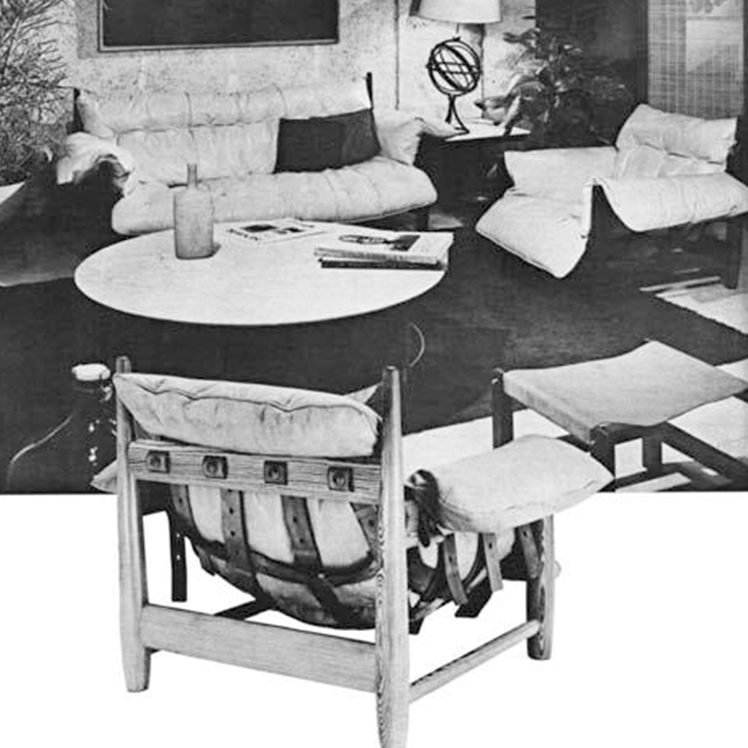 Interior room. An armchair and sofa sit in the background. A low-lying coffee table sits in the center. The sofa and armchair consist of a white cushion sitting on a dark timbre frame. A Vase and magazine sit on top of the coffee table. In the foreground, there is a wooden framed chair, with a cushion sitting in the frame. There is a matching foot-stool made of wood and canvas.