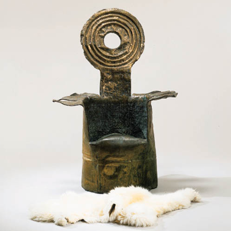 A seat cast in bronze. The bronze seat takes a sculptural appearance. It's reminiscent of an opened can, with the top of it acting as the backrest. There is a white fur rug on the ground beside it.