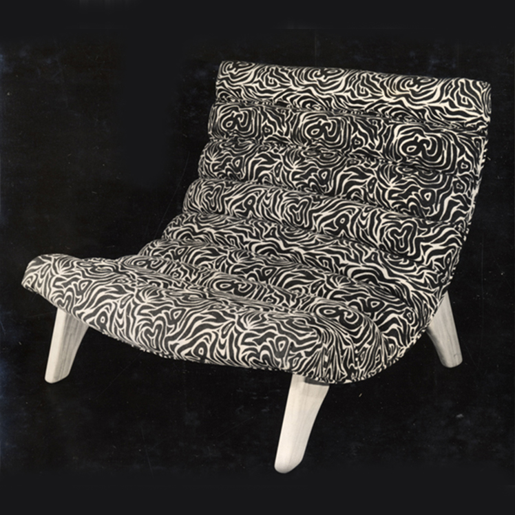 Curved cushioned, upholstered modern armchair. Black and white design. White low-lying wooden legs. Black background.