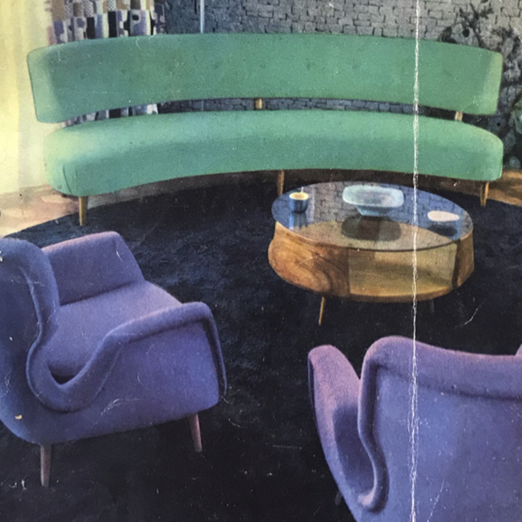 An interior scene of a sitting room. Modern, teel colored, slightly curved sofa, with a contrasting minimalist golden construction. Two armchairs in a deep purple with a curved back and armrest. A center, low-lying coffee table made of glass. All of the furniture sits on a round deep blue carpet.