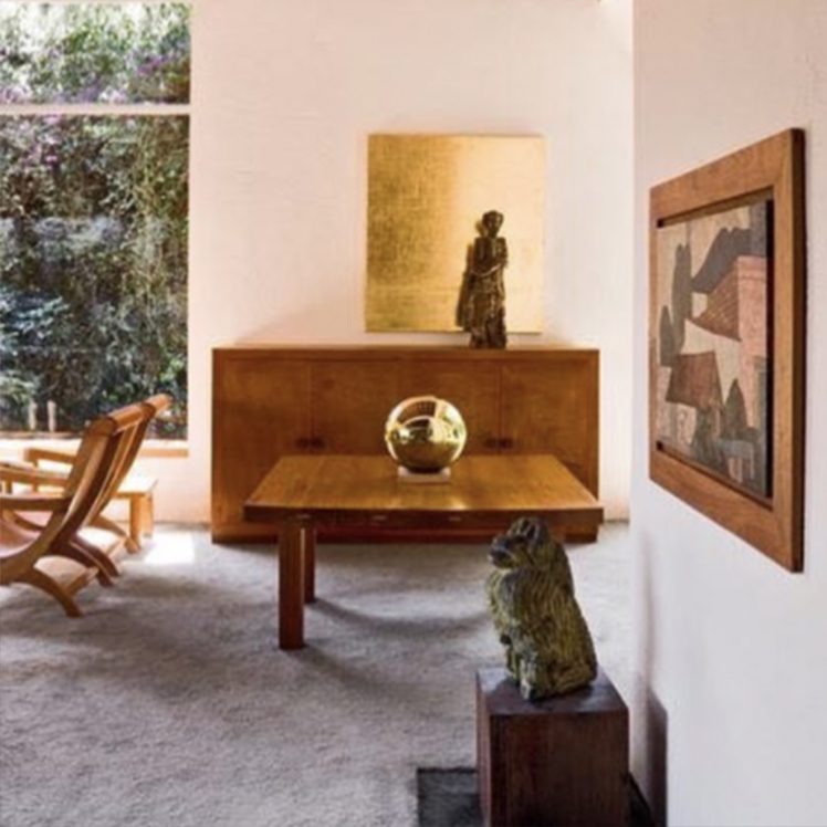 Casa Pedregal, México. Interior scene. A low-lying mahogany coffee table with a spherical golden sculpture resting on top. A matching cabinet with a sculpture of a woman. A golden painting on the wall. Grey carpets. A large window to the left.