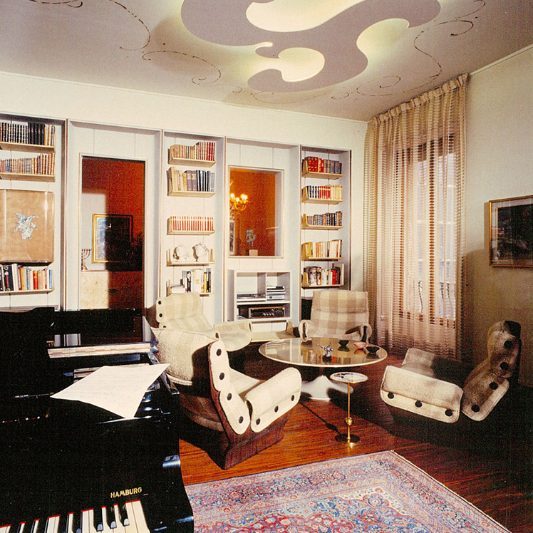 Interior scene of a sitting room. Four beige armchairs are centered around a low coffee table. A piano sits in the foreground. The piano sits on a Persian rug. The back wall is used as a library. A decorative, abstract light hangs from the ceiling. A doorway and an indoor window punctuate the back wall.