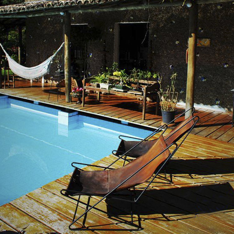 Casa Cirell, an external wooden terrace with a pool. A raised wooden terrace above the pool, the pillars of the house are founded in the pool. Beside the pool, are two of Bo Bardi's leather and lounge chairs.