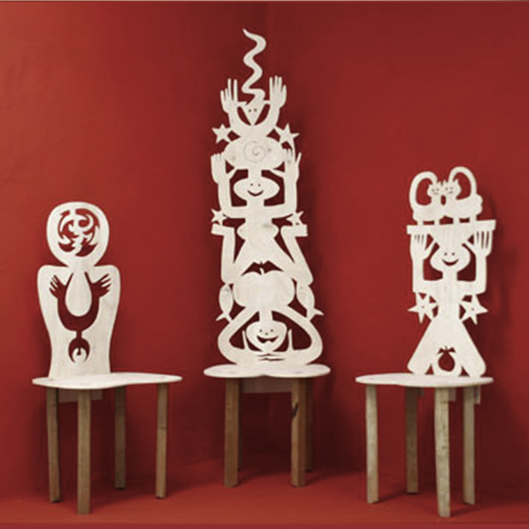 Red interior room. Three sculptural chairs. The base of the chairs are wooden. The white backrest of the chairs consists of a series of abstract faces and sculptural forms. The center chair has the longest backrest, with three sculptural forms piled on top of one another.