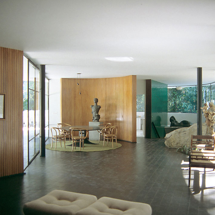Interior hall and dining area. Two simple, black columns support a white roof. A curved, wooden wall partition folds slightly around a dining table in the background of the image. A floor-to-ceiling glass-paneled wall allows light to access the room. Various modern sculptures decorate the room. The floor is a ceramic, black brick. A white upholstered futon sits at the foreground of the image.