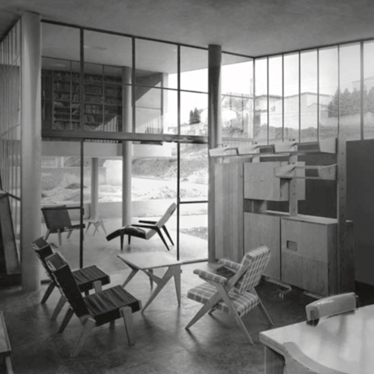 Lina Bo Bardi's furniture in João Vilanova Architect piece, 1940's Brazil. An interior space, with a table and three armchairs.